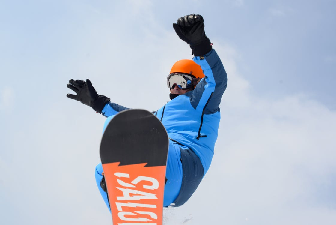 A man flying through the air while riding a snowboard